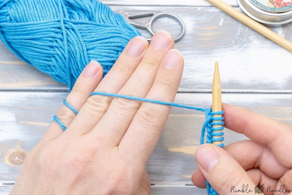 bringing yarn across the back of the hand to tension the yarn in preparation for the knit stitch