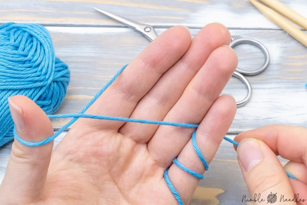 securing the tail between the ring and pinky finger as a preparation