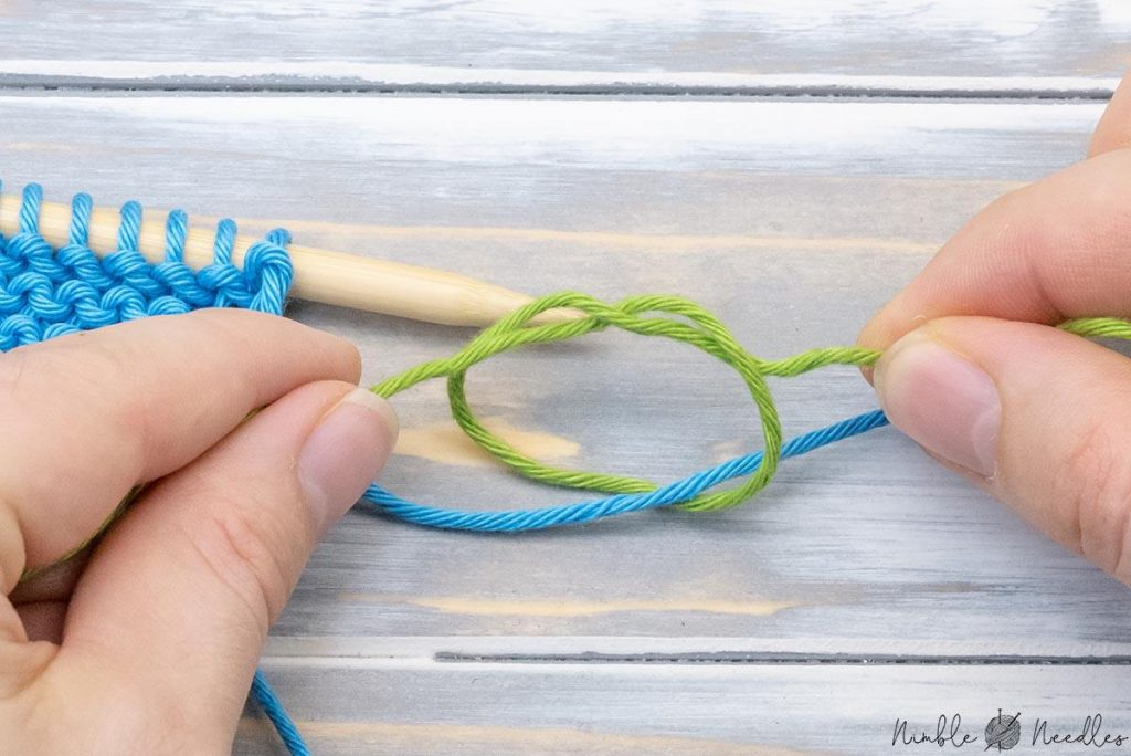 tying a knot around the new with the new yarn to ada new ball